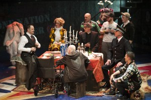 """Macheath (Mitchell Jarvis, left) holds court on his wedding day (from left clockwise: Erin Driscoll, Sean Fri, Thomas Adrian Simpson, Paul Scanlan, John Leslie Wolfe, Ryan Sellers, and Rick Hammerly). """"The Threepenny Opera"""" is now playing at Signature Theatre through June 1, 2014. Photo by Margot Schulman."""