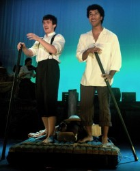 "Huckleberry Finn (Brian Nabors) and Jim (Alex Peças) pole their raft down the Mississippi River while singing about the ""Muddy Water."" Photo provided by Silhouette Stages."