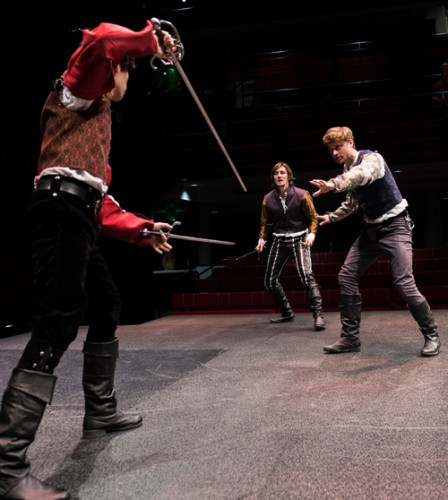 Brawls with knives and swords distrupt the streets of Verona. Here, Romeo (right) tries to halt a battle between his friend Mercutio (center), and his enemy Tybalt, a Capulet (left). David Mavricos is Romeo, Vince Eisenson is Mercutio, and Rafael Sebastian is Tybalt.